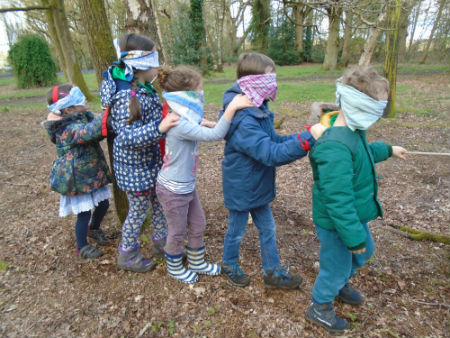 Elfins playing in the woods wearing blindfolds
