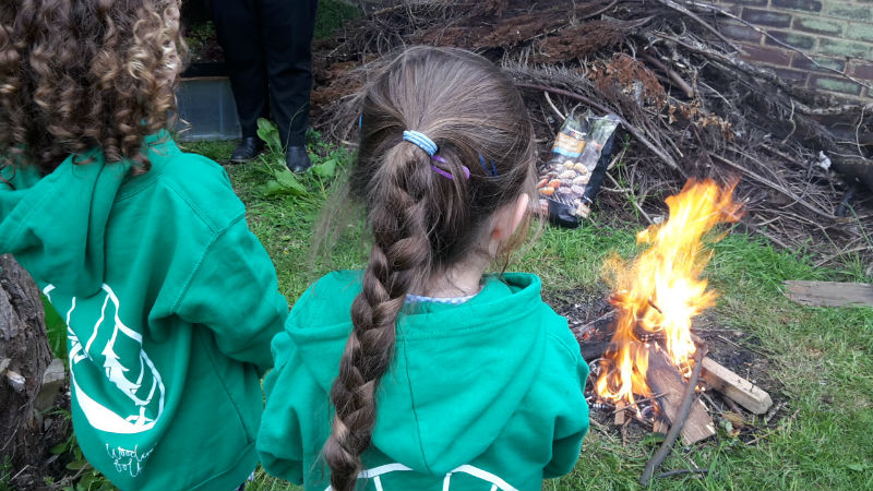 Girls campfire making pizza